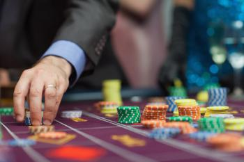 Käsi asettamassa pelimerkkiä pöydälle